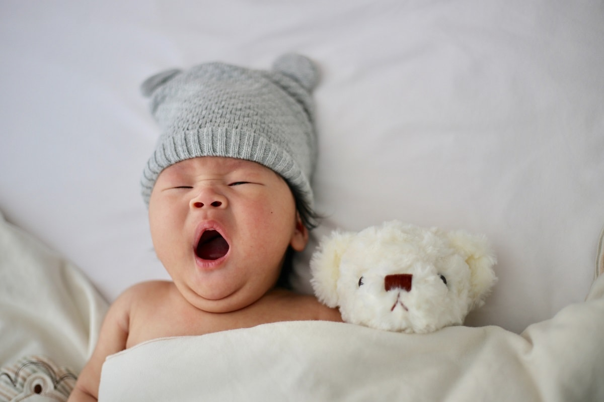Mini-Tipps: München mit Baby im März: Baby kuschelt mit Bär und gähnt // HIMBEER